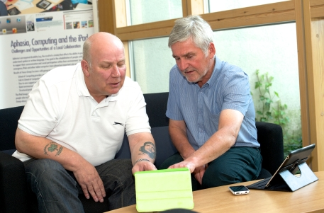 Eddie (right) says using an iPad to communicate has made a big difference.